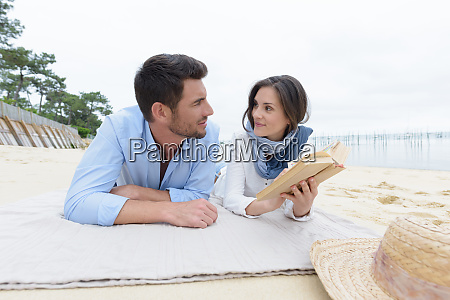 paar liest ein buch am strand