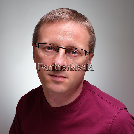caucasian man with glasses and serious