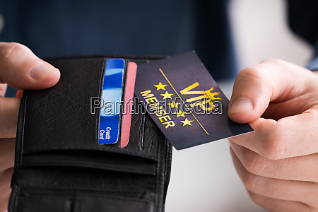 man removing vip member card from