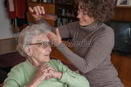 seniorin bekommt ihre haare gestylt von