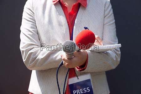 reporterin bei pressekonferenz notizen schreiben mikrofon