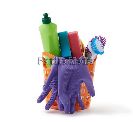 orangefarbener korb mit waschschwaemmen gummischutzhandschuhen buersten
