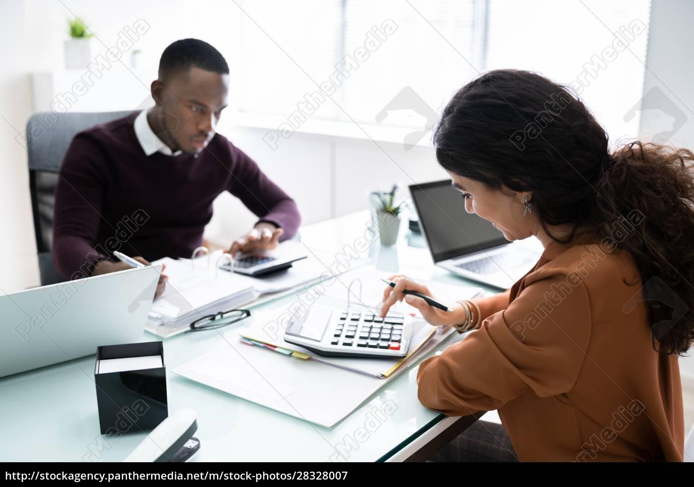 zwei, geschäftsleute, mit, taschenrechner, am, arbeitsplatz - 28328007