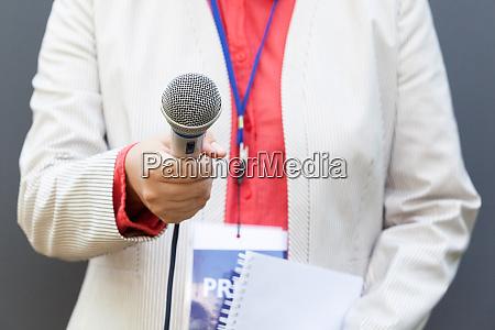 journalist haelt mikrofon und gibt medieninterview