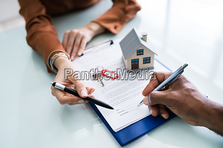 person hand signing vertrag mit schluesseln