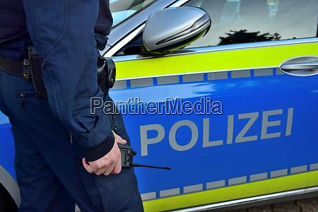 ein polizist neben einem deutschen polizeiauto