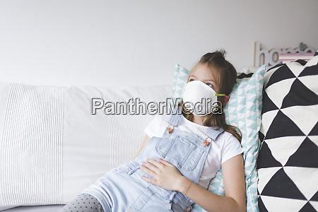 junges maedchen mit weisser schutzmaske zu