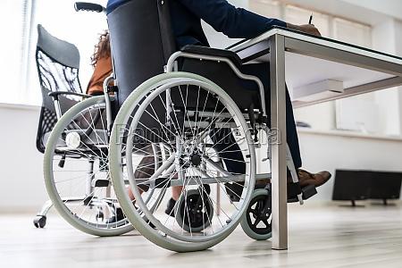 behinderter geschaeftsmann sitzt auf rollstuhl