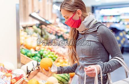 frau beim einkaufen im supermarkt waehrend
