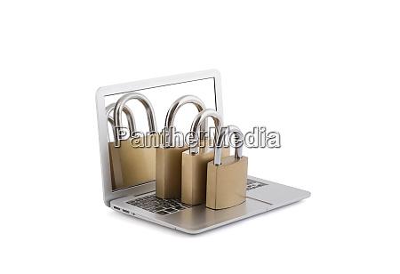 computersicherheitskonzept drei vorhaengeschloesser auf laptop isoliert