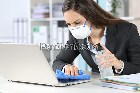 executive with mask cleaning laptop with