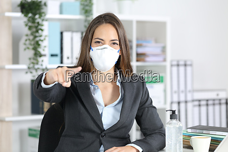 executive with mask pointing at you