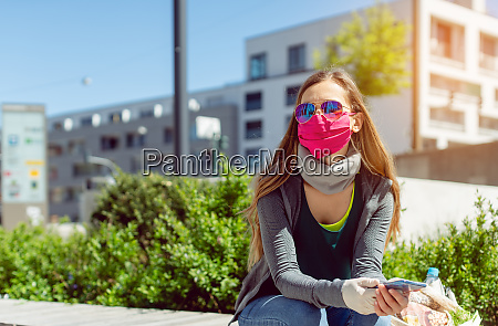 woman with face mask sitting outside