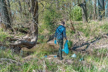 freiwilliger sammelt plastikmuell in der natur