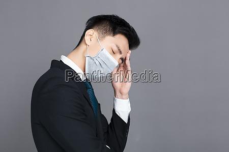 junger mann traegt medizinische maske und