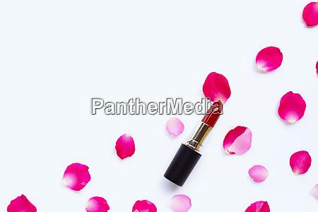 lippenstift mit rosenblaettern isoliert auf weissem