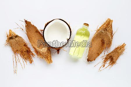 kokosoel mit kokosnuessen auf weissem hintergrund