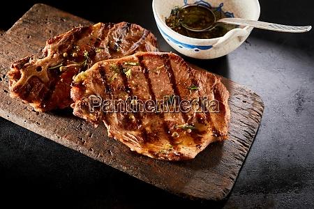 gegrillte steaks auf holzbrett mit seitensauce