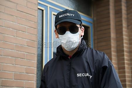 sicherheitsmann steht in gesichtsmaske