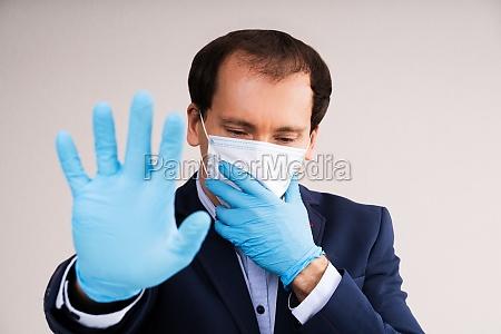 mann in maske leidet unter panikattacke