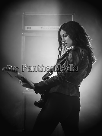 beautiful woman on stage playing guitar