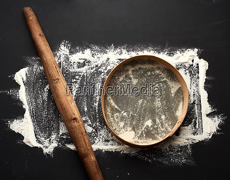 weisses weizenmehl auf einem schwarzen tisch