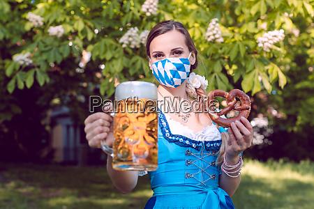 bayerische frau toastet mit bier waehrend
