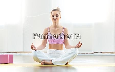 schoene frau meditieren in yoga pose