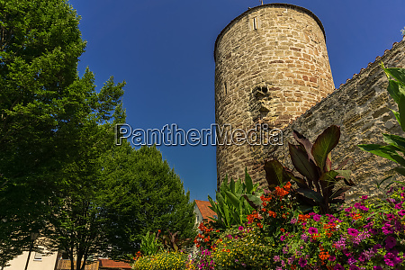 an old watchtower with flowers below
