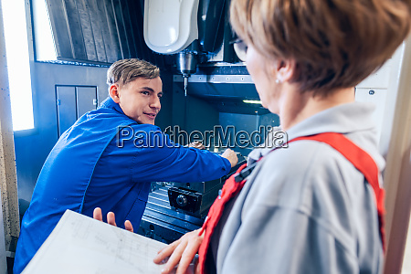 supervisor beobachtet junge arbeiter aendern einrichtung