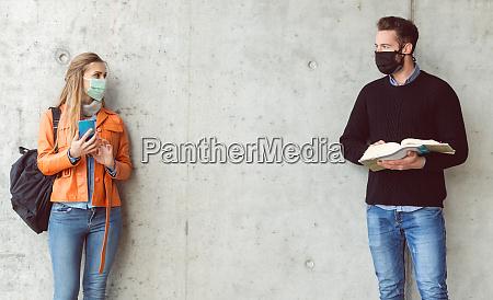 zwei studenten stehen in sozialer entfernung