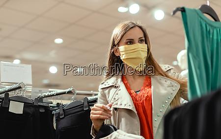 frau einkaufen in modegeschaeft tragen gesichtsmaske