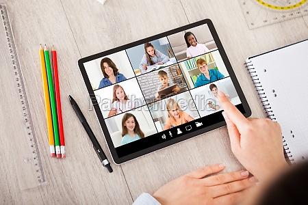 person mit digitalem tablet und studentenzubehoer