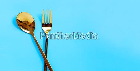 goldener loeffel und gabel auf blauem