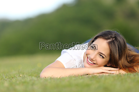 happy woman lying on grass looking
