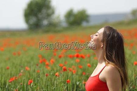 satisfied woman breathing fresh air on