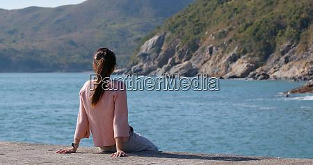 frau sitzt am meer und schaut