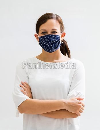 frau in wiederverwendbaren tuch gesichtsmaske covid