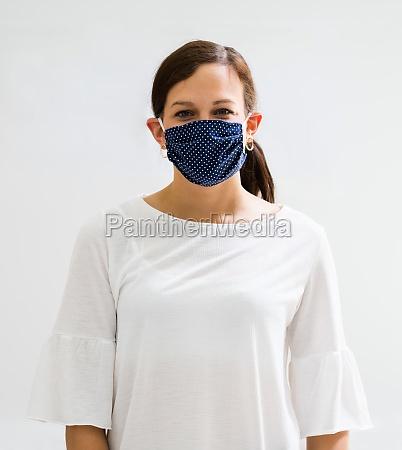 frau in wiederverwendbaren tuch gesichtsmaske