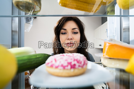 happy young woman looking at donut