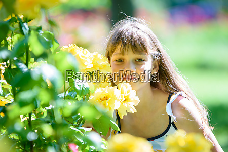girl in the park sniffs yellow