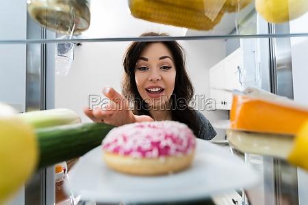 glueckliche junge frau die donut aus