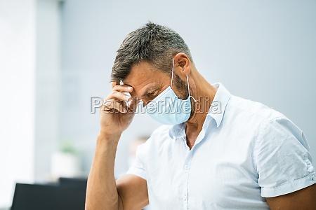 gestresster mitarbeiter im buero traegt maske