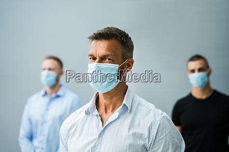 gruppe von bueroangestellten die gesichtsmasken tragen