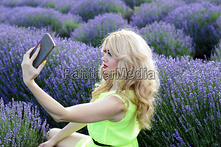 eine frau fotografiert in den lavendelbueschen