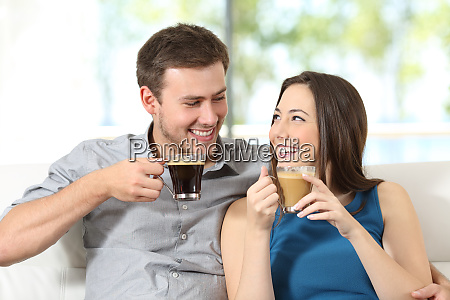 happy couple with coffee cups looking