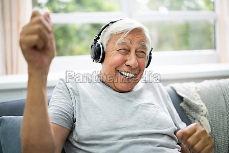 laechelnde aeltere senioren hoeren musik
