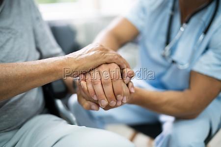 elder patient hilft krankenschwester hand