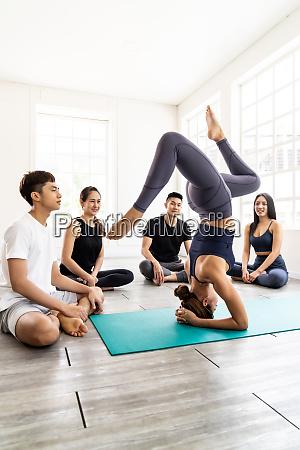 yoga lehrer zeigen kopfstand pose fuer