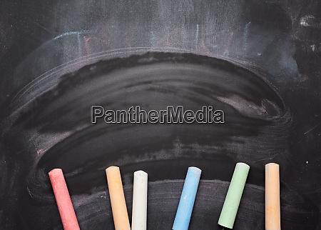 mehrfarbige kreide auf leeren schwarzen kreidetafeln